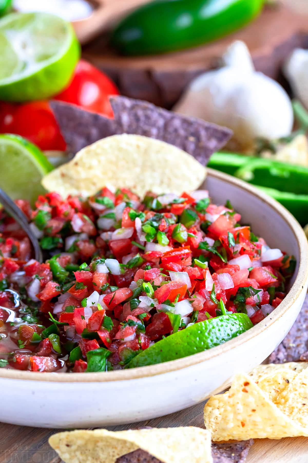 beautiful salsa in white bowl with lime wedges and tortilla chips.