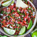 top down view of pico de gallo in clay bowl garnished with lime wedges and surrounded by chips.