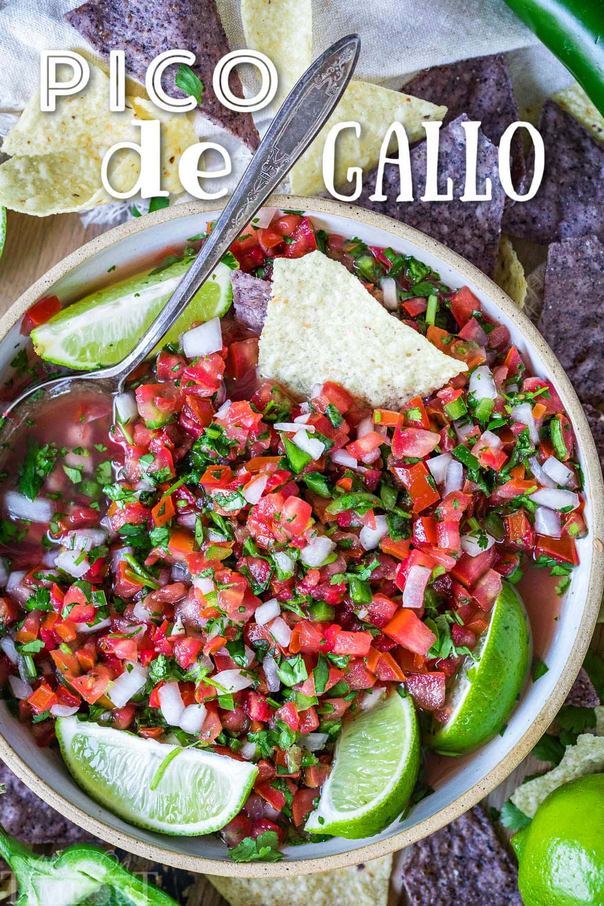 top down view of pico de gallo in clay bowl garnished with lime wedges and surrounded by chips. title overlay at top of image.