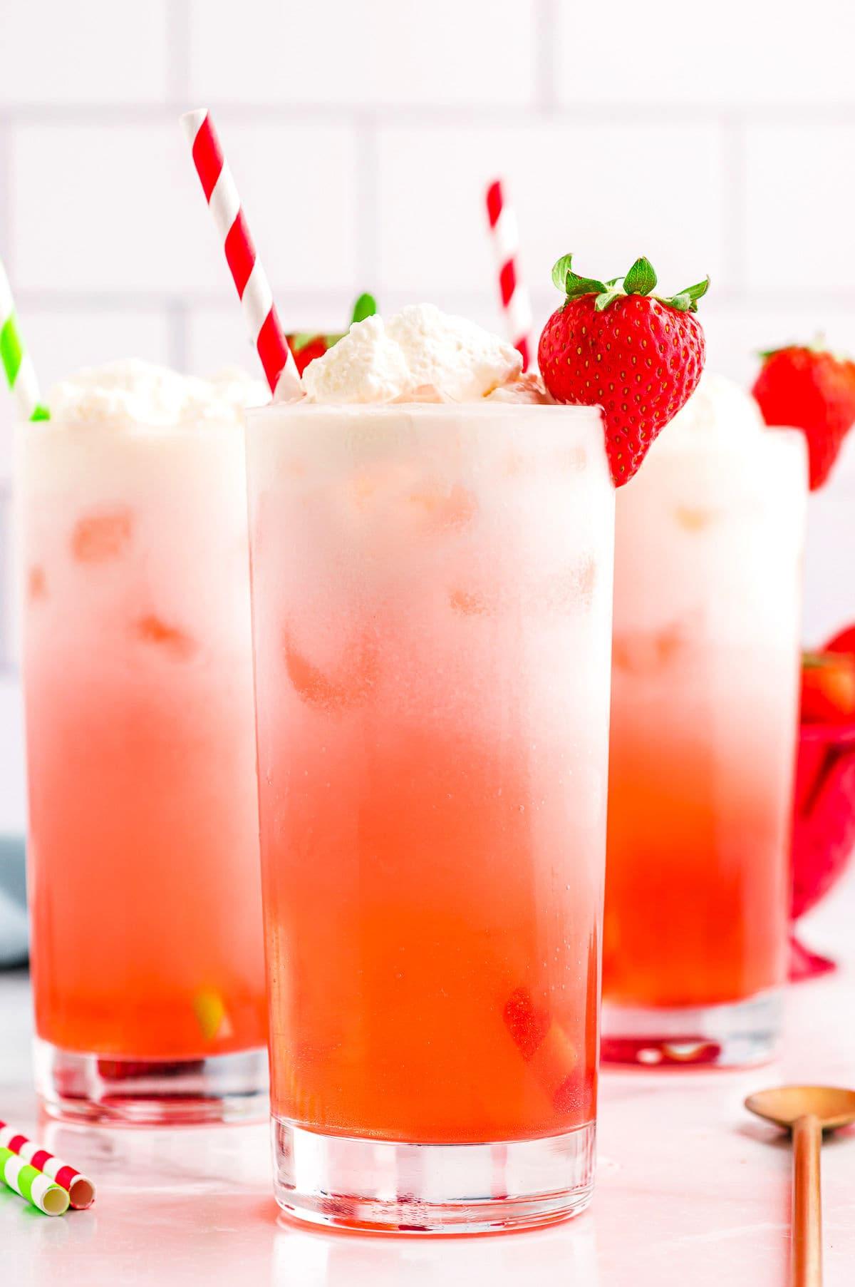 strawberry Italian cream sodas in tall beverage glass with paper straws.