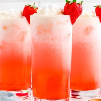 strawberry italian sodas in tall glasses garnished with whipped cream and fresh strawberries.