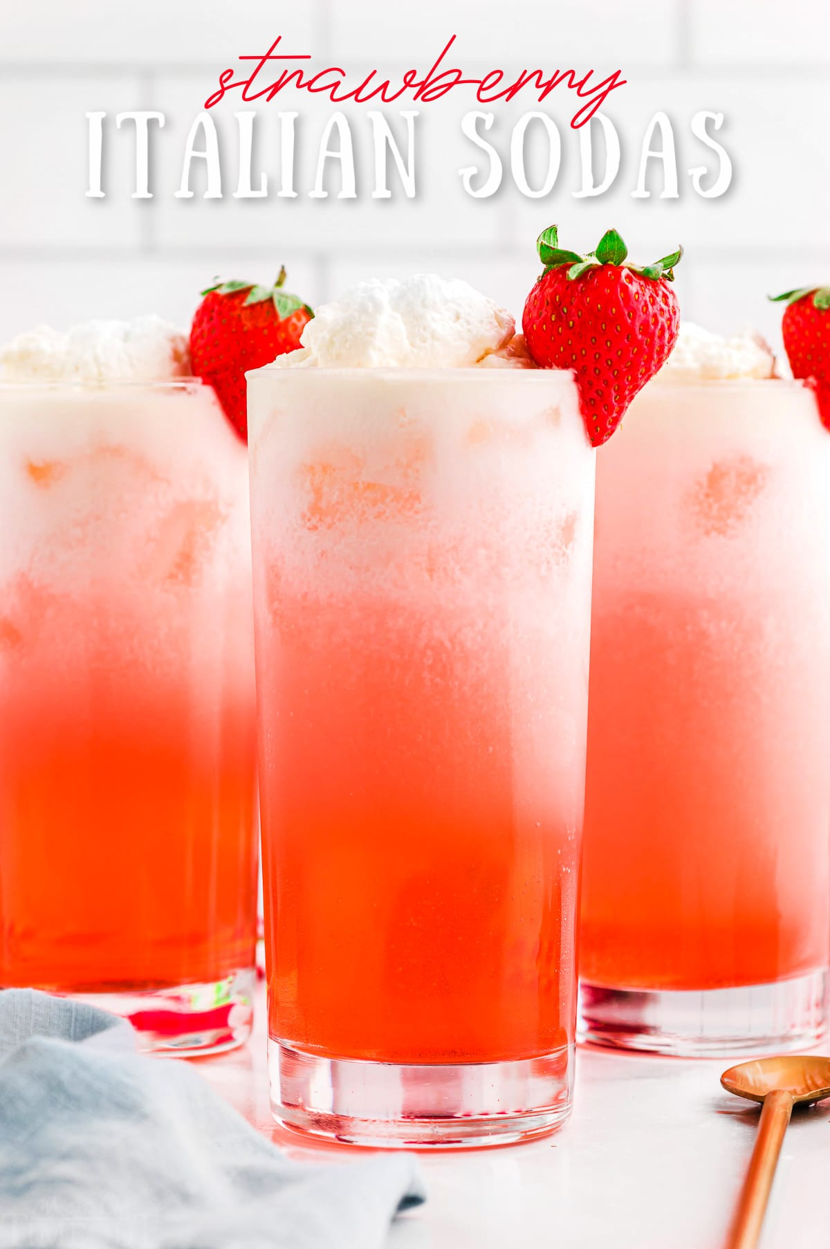 strawberry italian sodas in tall glasses garnished with whipped cream and fresh strawberries. title overlay at top of image.