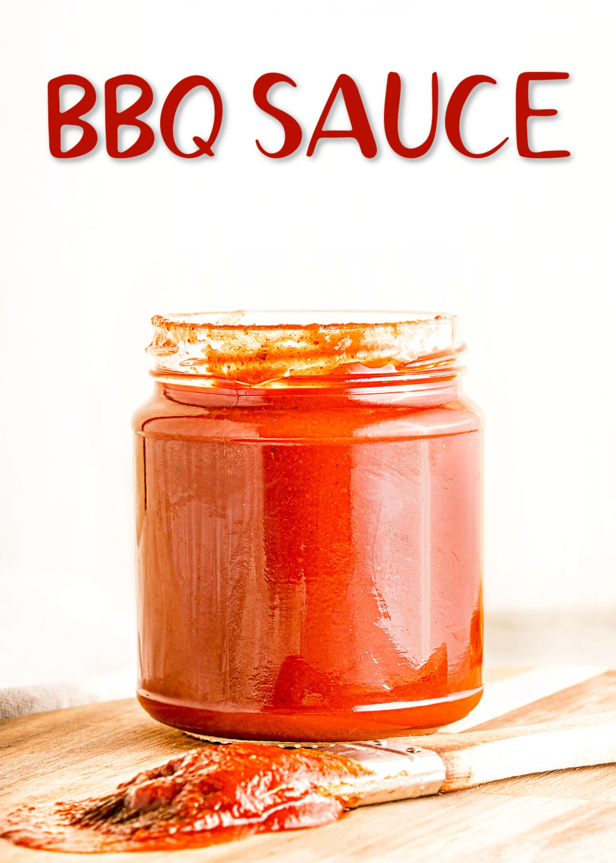 homemade bbq sauce is glass jar sitting on wood cutting board with title overlay at top of image.