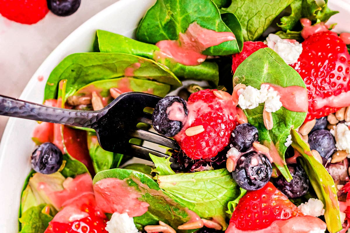 forkful of berry salad with spinach and goat cheese in bowl.