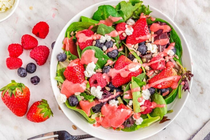 top down look at berry salad with raspberry vinaigrette dressing on white plate.
