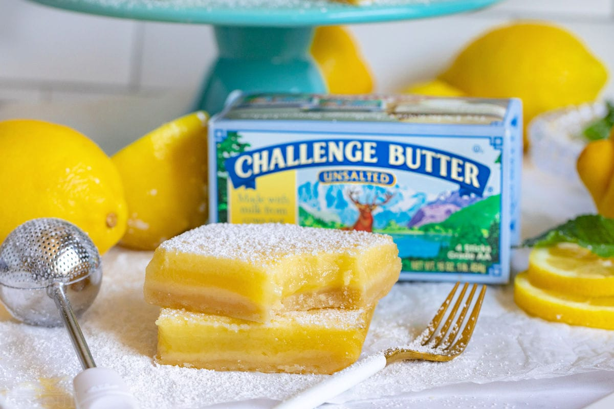 two lemon bars one with a bite taken out of it. box of challenge butter behind bars.