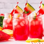 three large canning jars filled with watermelon lemonade and topped with watermelon wedges.