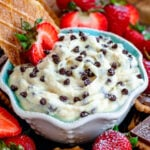 cannoli dip with chocolate chips sprinkled on top in a small white bowl with blue interior surrounded by cookies and strawberries ready to be enjoyed.