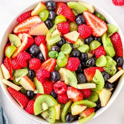 fruit salad in white bowl ready to serve with title overlay at top of image. fruit salad has kiwis, strawberries grapes and more.