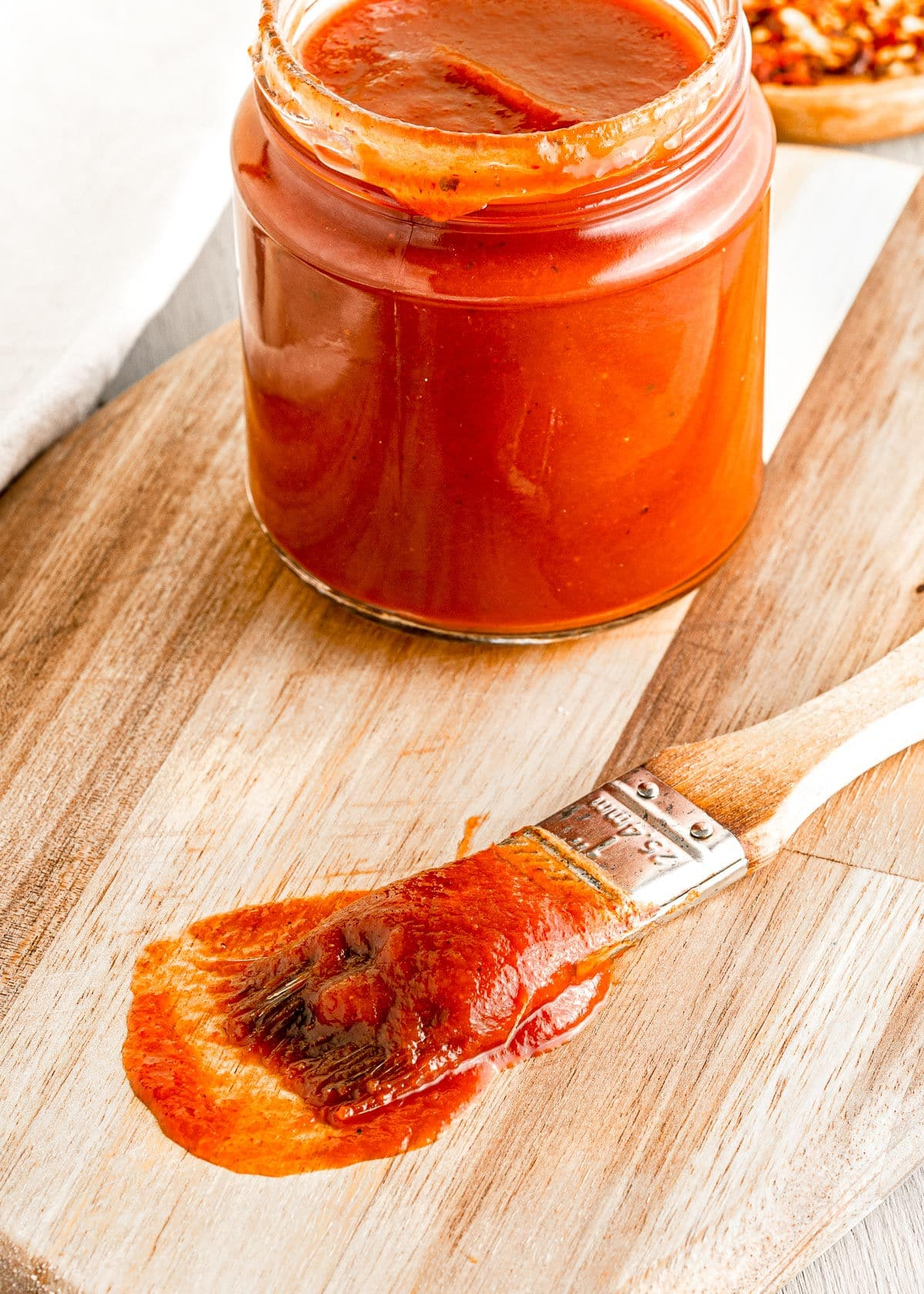 brush with bbq sauce on it sitting on cutting board next to a jar of bbq sauce.