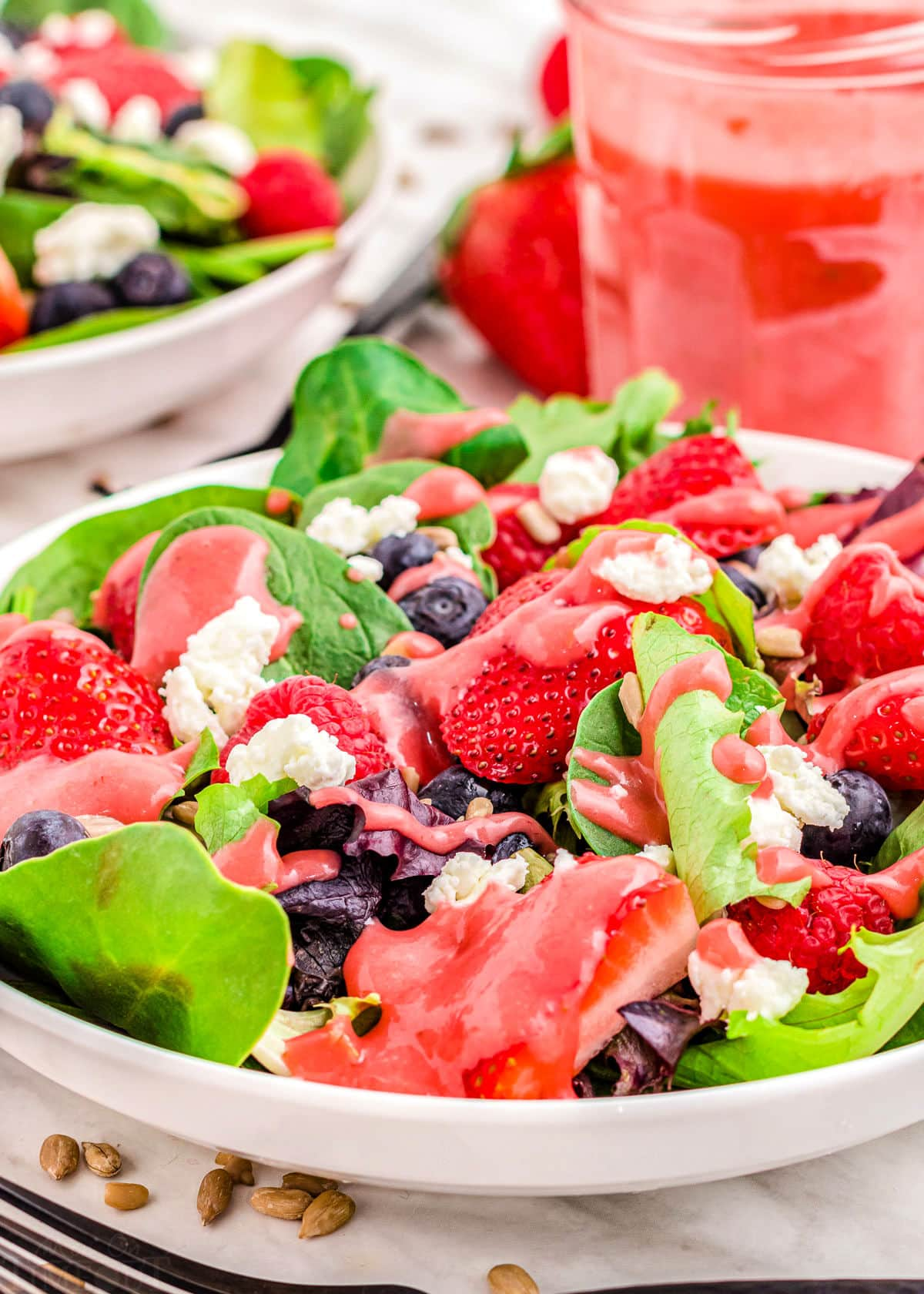 ready to enjoy summer berry salad with raspberry vinaigrette in jar in background.