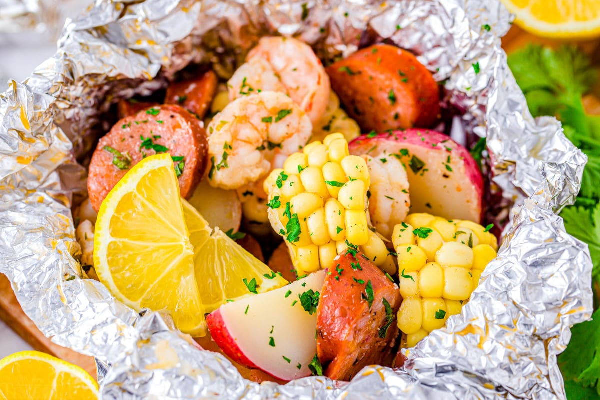 close up look at shrimp foil packets with corn, potatoes, shrimp, sausage and herbs.