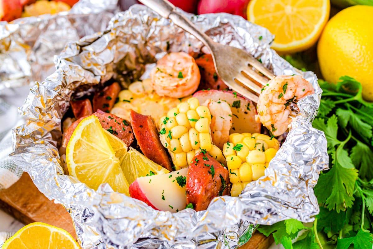 shrimp boil foil packs opened up and a shrimp on a fork ready to eat.