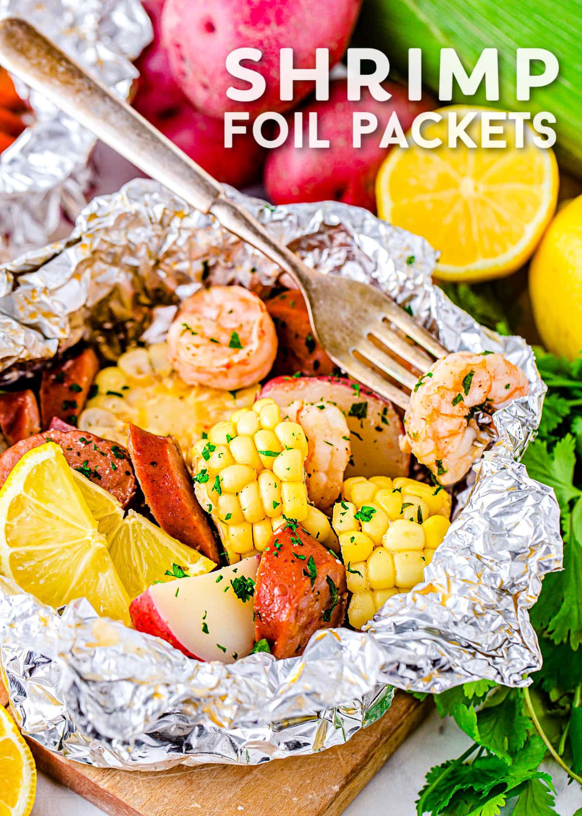 shrimp boil cooked in foil with corn, sausage, shrimp and potatoes. Title overlay at top of image.