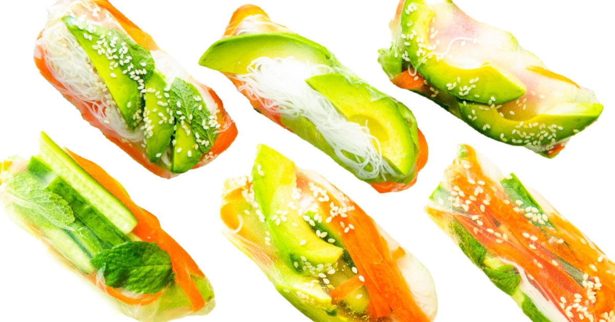 6 spring rolls on white background all rolled and ready to enjoy. Made with avocado and carrots.