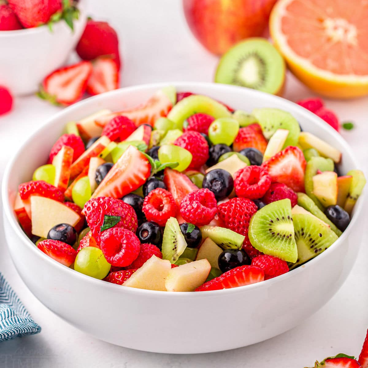 light and refreshing fruit salad with summer fruits in large white serving dish.