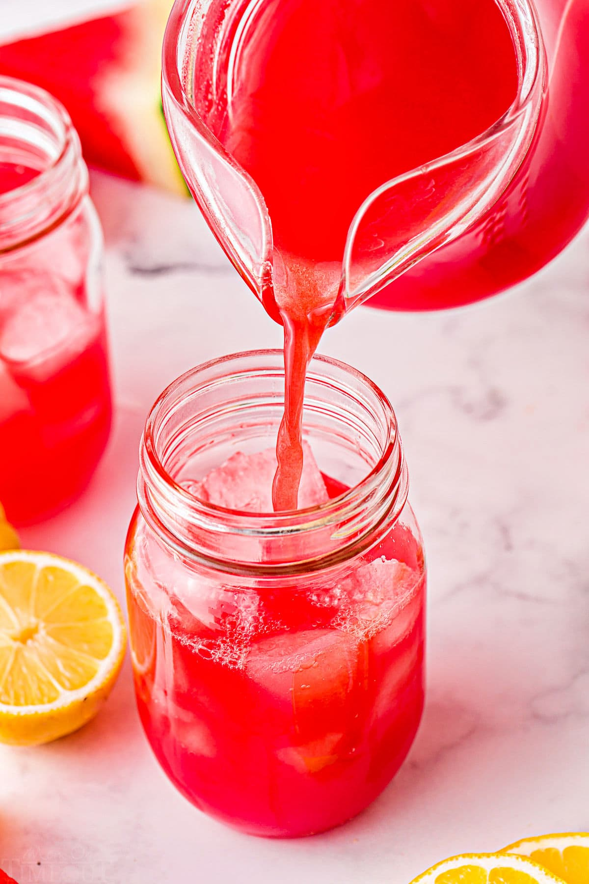 watermelon lemonade being poured into large glass.