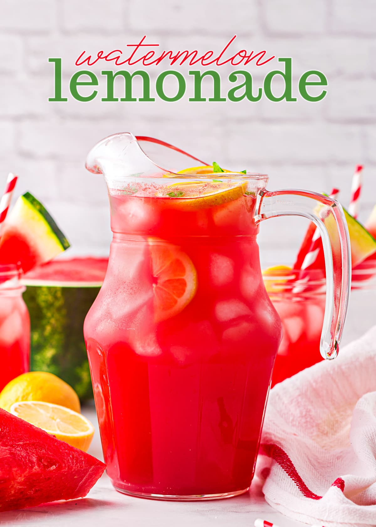 watermelon lemonade in a tall glass pitcher with watermelon slices and lemons scattered about. title overlay at top of image.