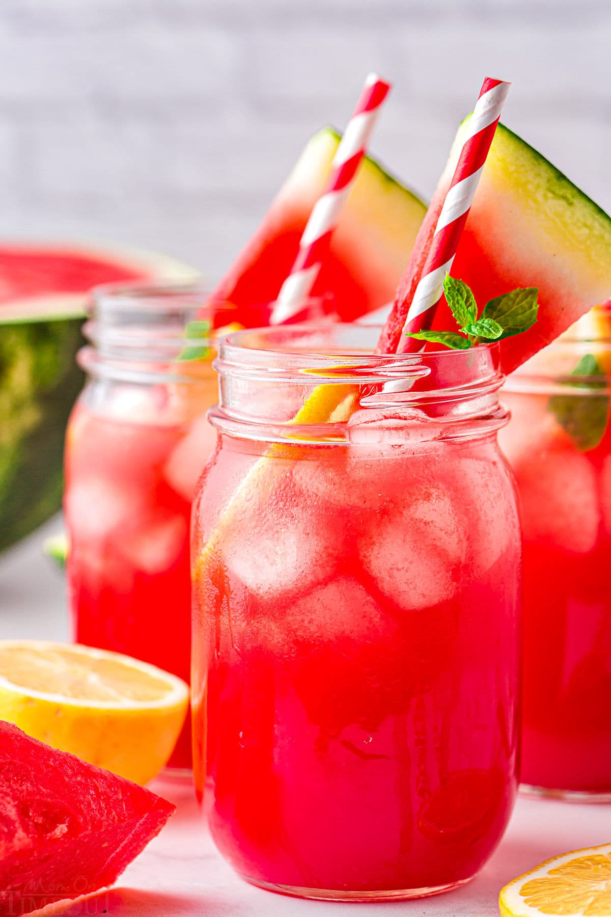 watermelon lemonade serve with striped straws and watermelon slices.