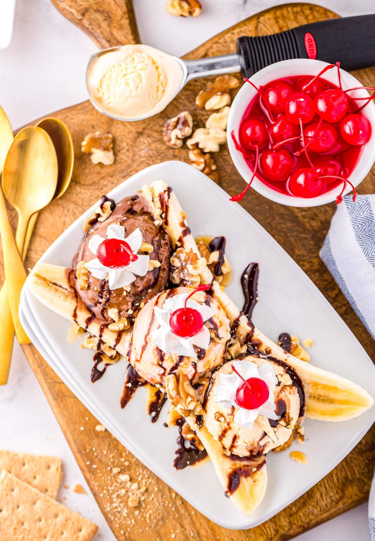 top down look at a classic banana split made with three different flavors of ice cream, whipped cream, and cherries. Plate is sitting on wood board next to a small bowl of maraschino cherries.