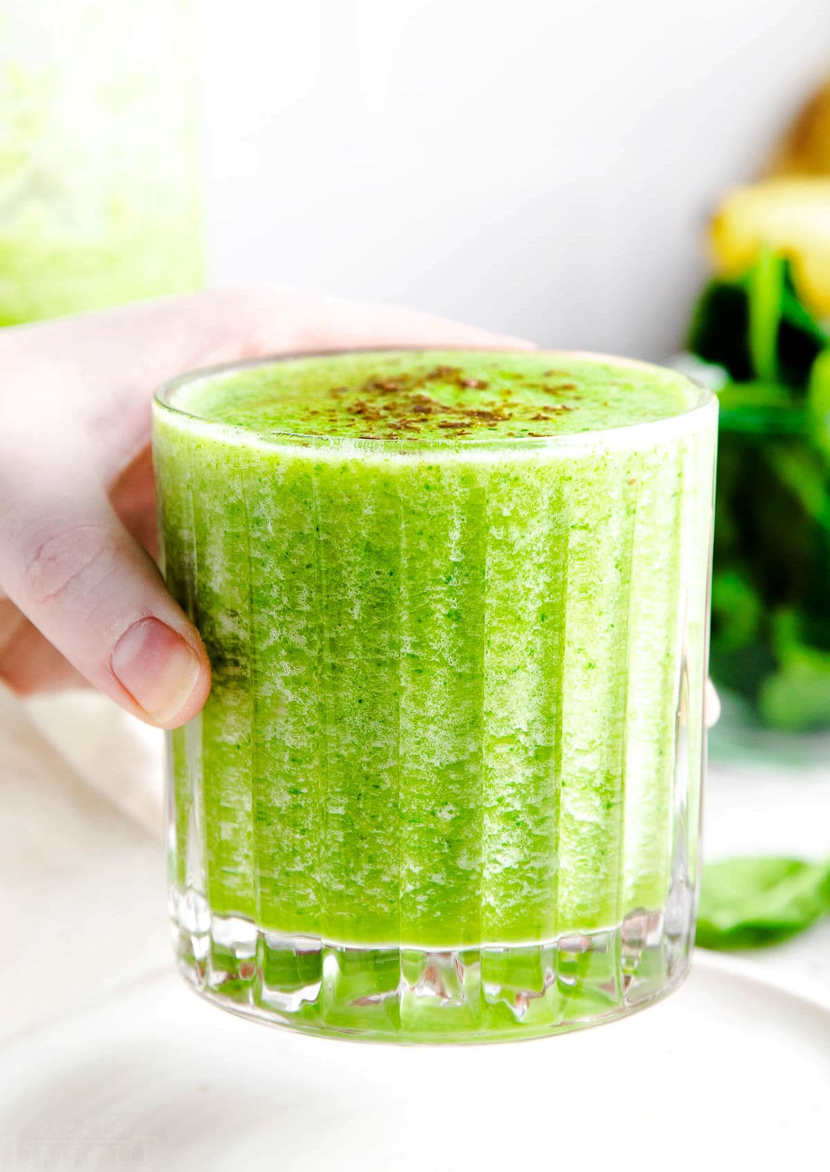 hand holding green smoothie in ridged glass with greens in the background.