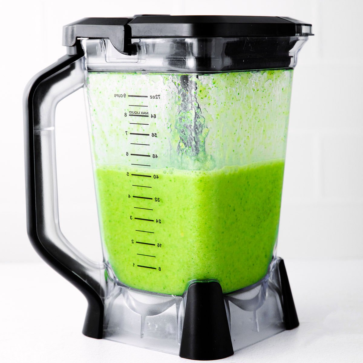 green smoothie in blender with black detailing. the color is bright and vibrant and the smoothie is ready to be served.