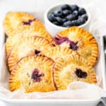 7 blueberry hand pies in a parchment lined sheet pan with fresh blueberries in a bowl in the back.