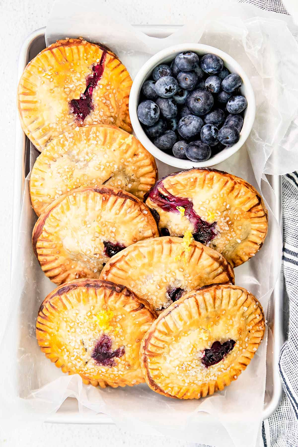 top down look at blueberry hand pies ready serve from small sheet pan with small bowl of blueberries nestled next to the pies.