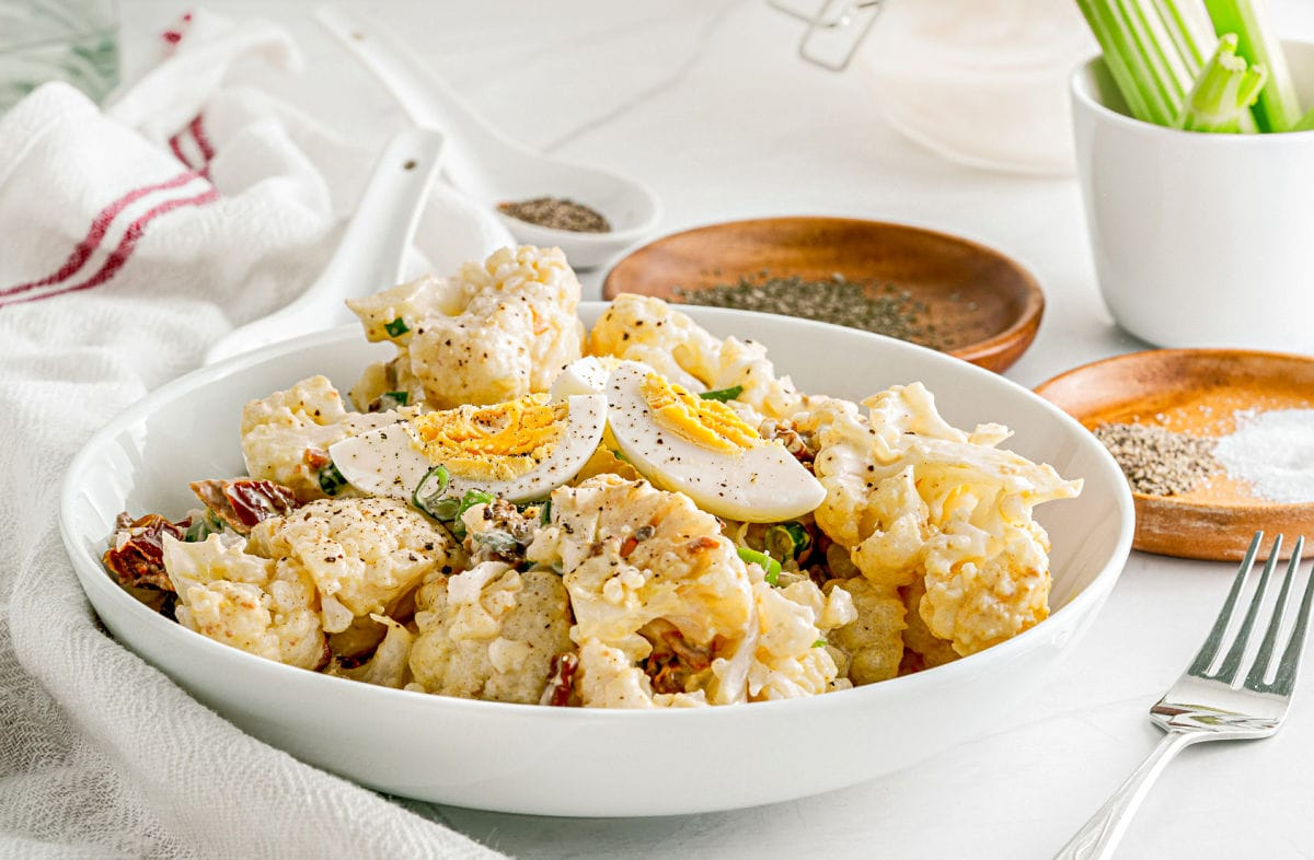 bowl of cauliflower potato salad topped with hard boiled egg quartered and sprinkled with pepper.