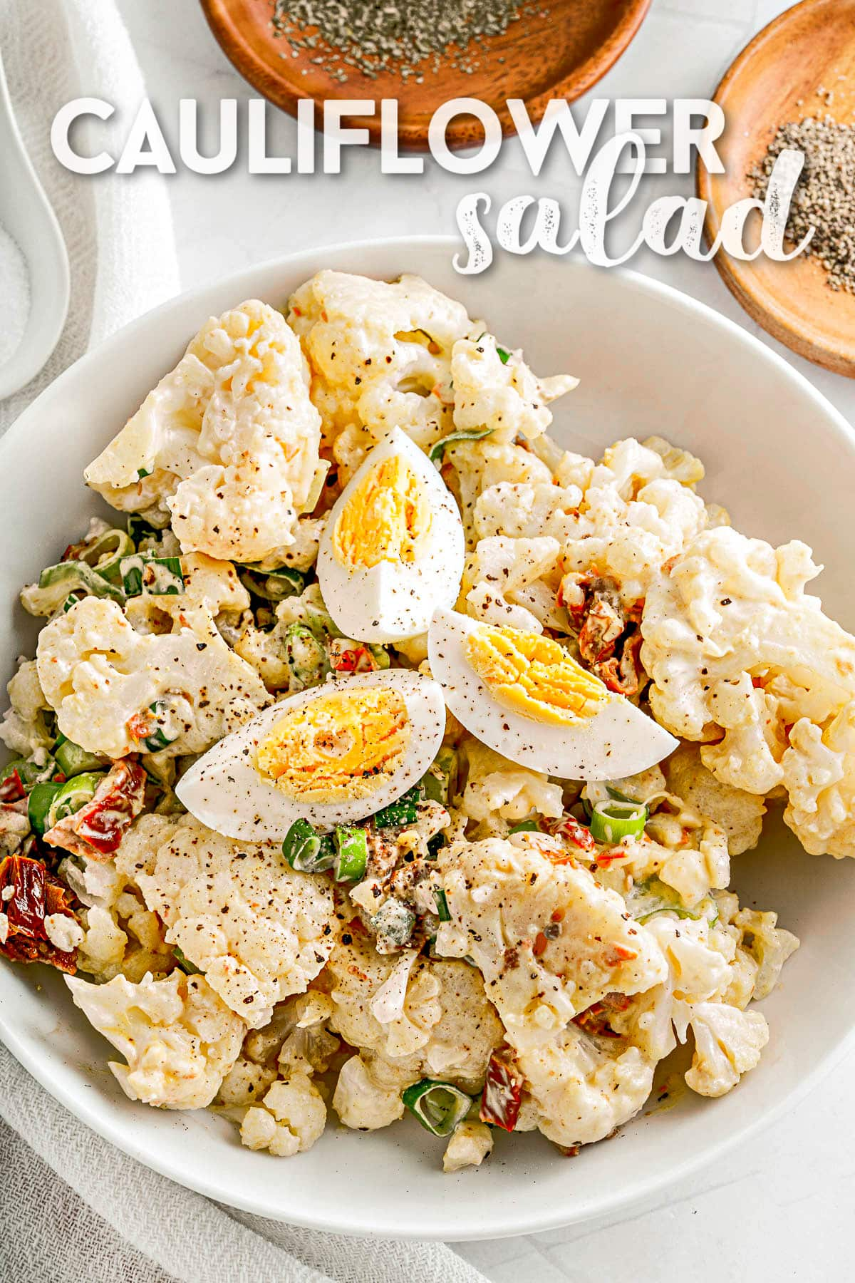 cauliflower salad made like a potato salad in white serving bowl and topped with slices of hard boiled egg. text overlay at top of image.