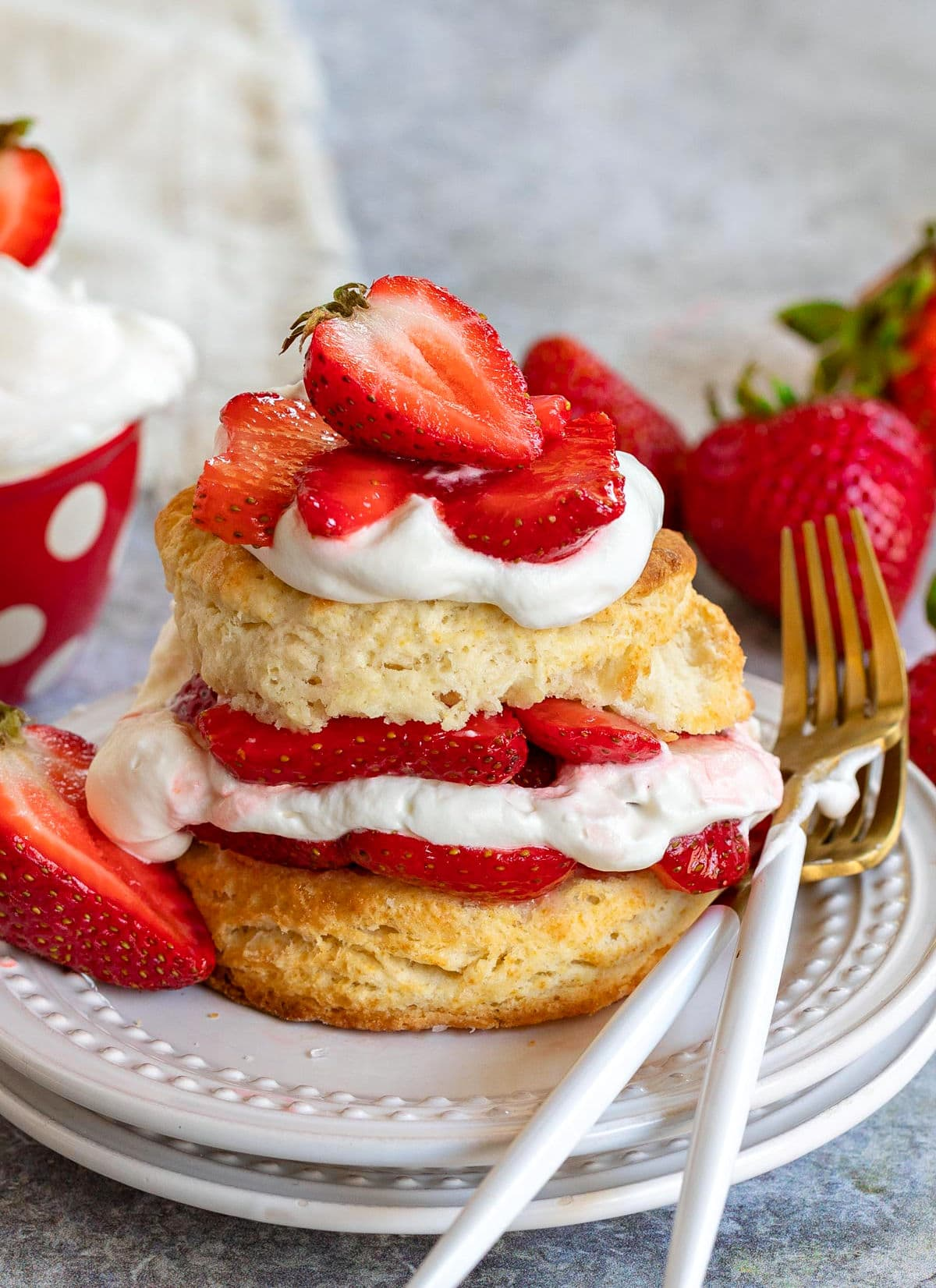 strawberry shortcake on white plate with layers of macerated strawberries and freshly whipped cream. two forks resting on the edge of the plate on one side and half a strawberry on the other. beige napkin in background.