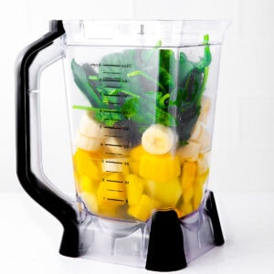 blender with green smoothie ingredients in it ready to blend.