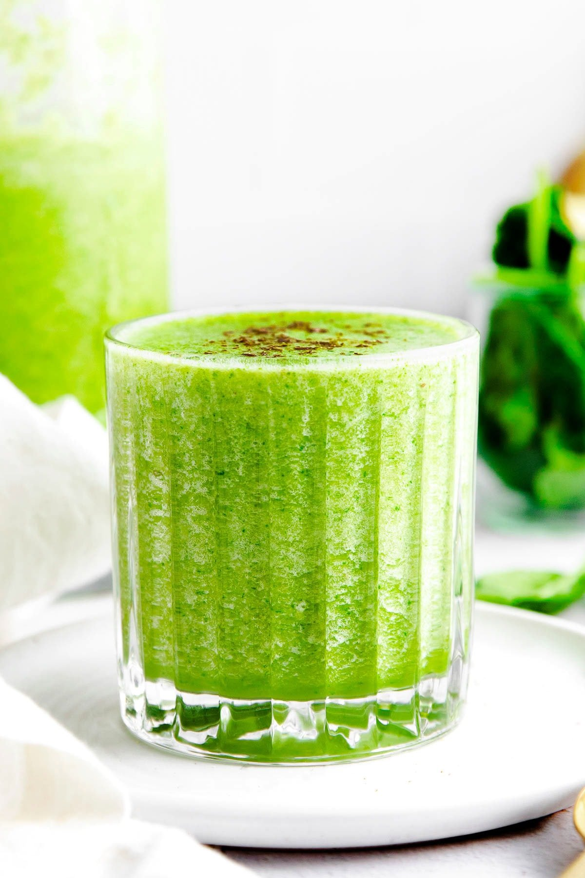 front view of small glass filled to the brim with a green smoothie.