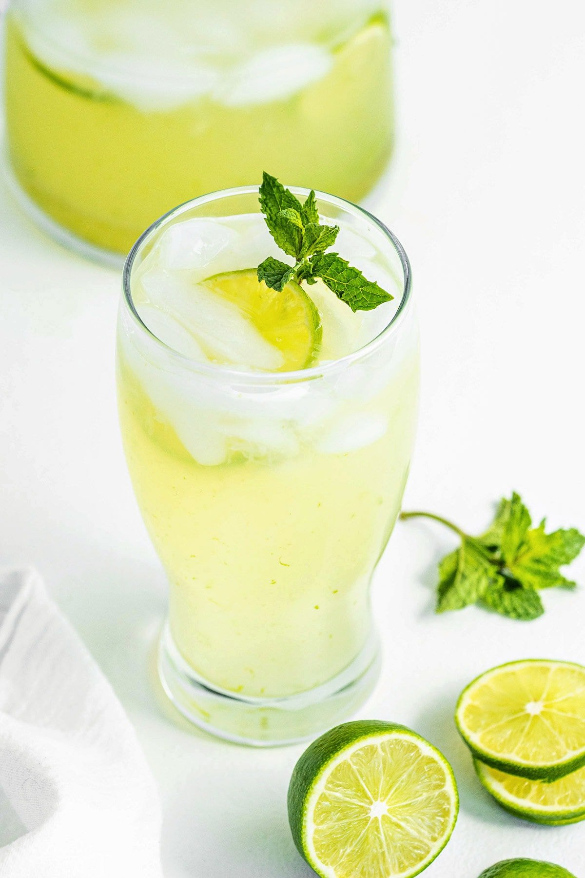 top down look at limeade in a tall clear glass topped with a sprig of mint.