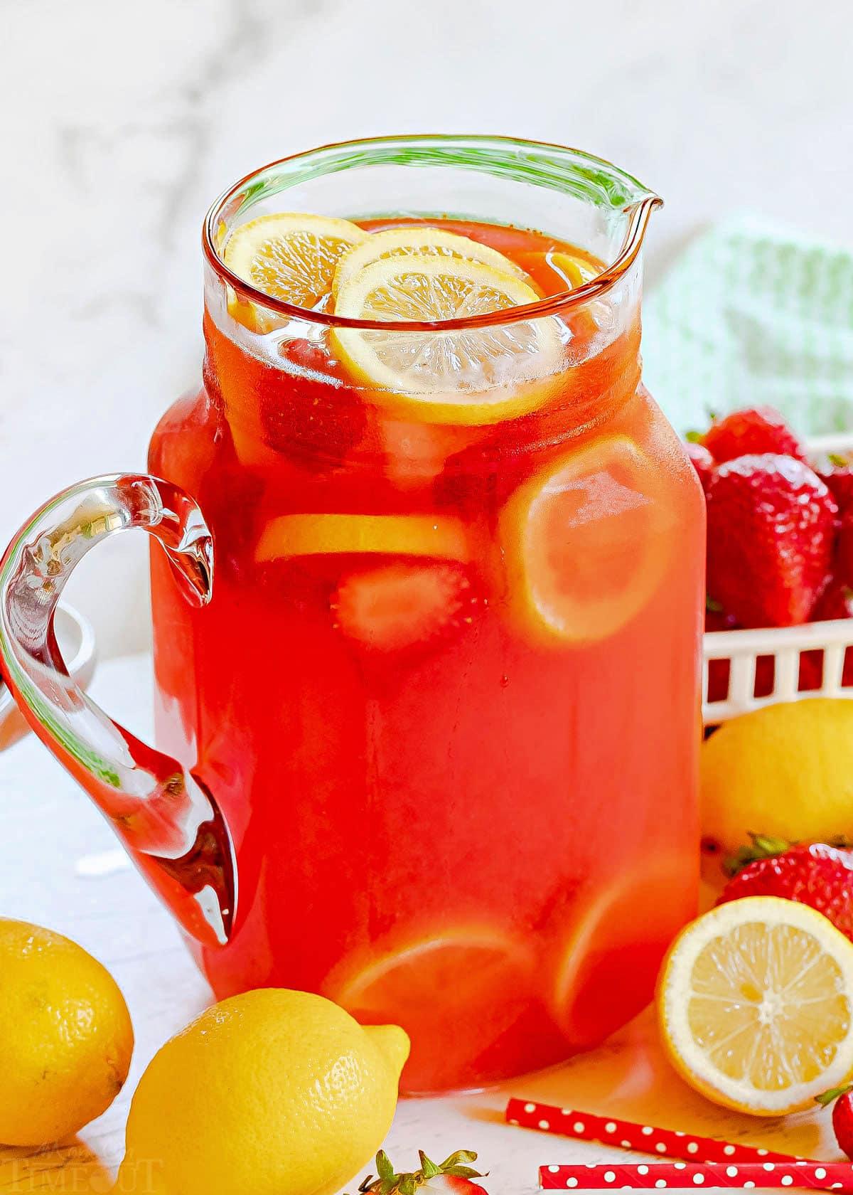 pitcher full of strawberry lemonade with fresh lemon slices and strawberries.