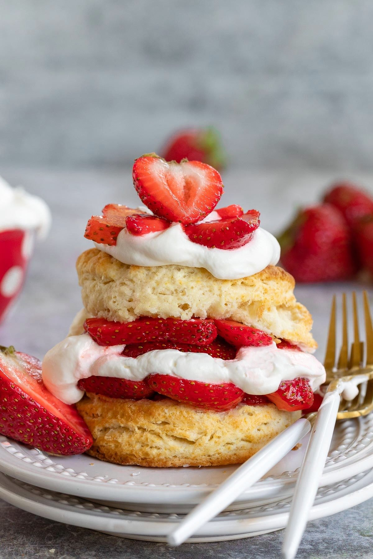 homemade strawberry shortcake on white plate with fresh macerated strawberries, whipped cream all layered on a split biscuit.