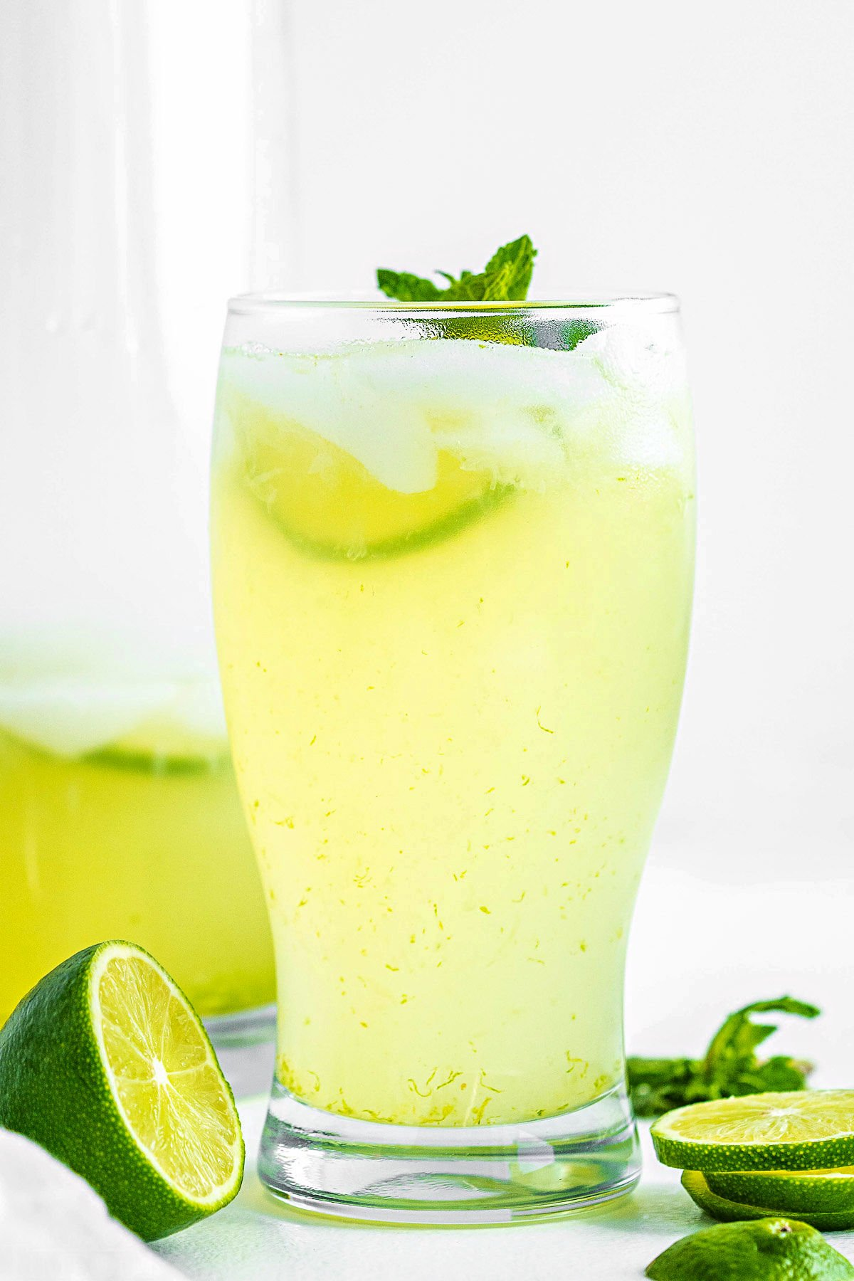 tall glass of freshly made limeade garnished with a sprig of mint and fresh lime slices sitting in front of pitcher of limemade.