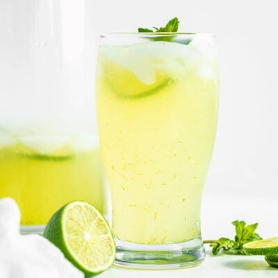 glass of limeade sitting in front of tall glass pitcher with more limeade in it. Fresh lime slices and mint sprigs scattered about.