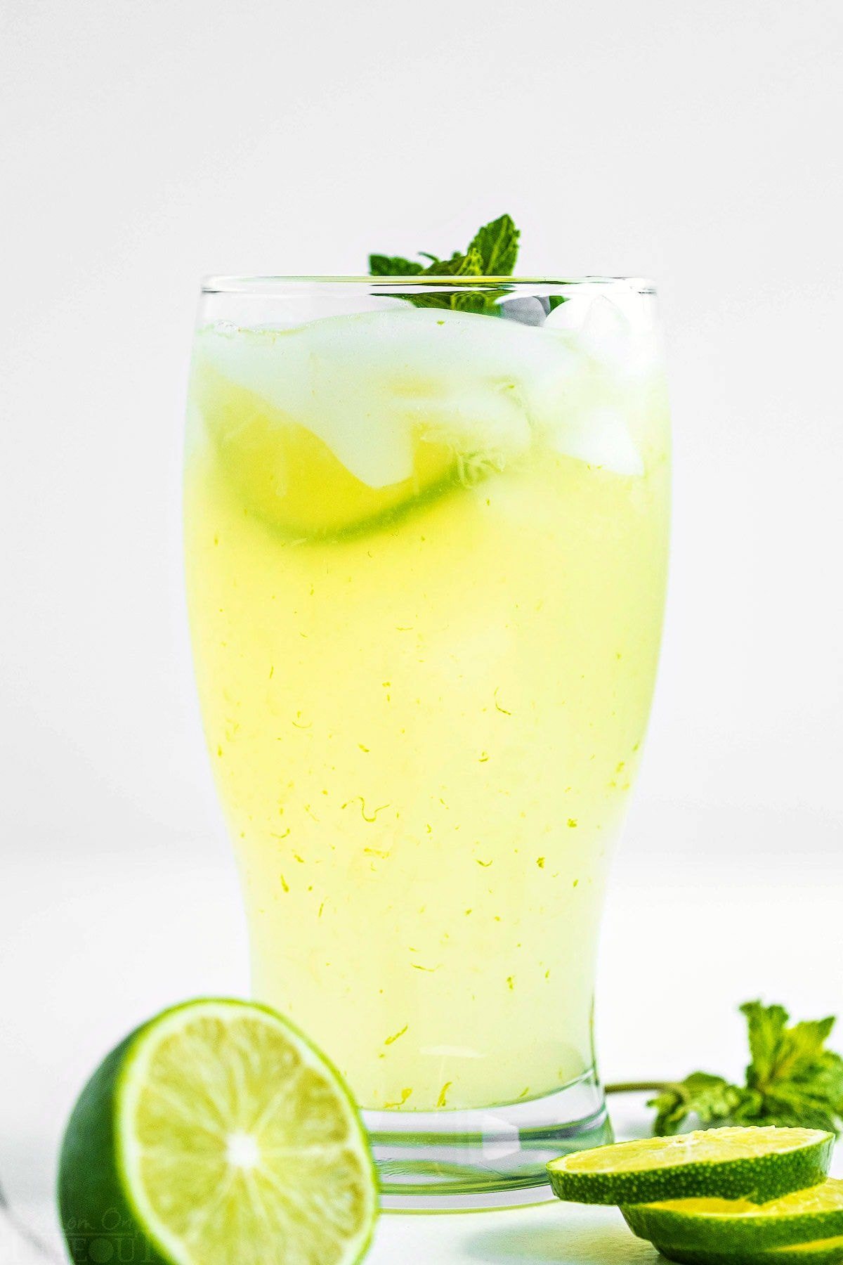 tall glass of freshly made limeade garnished with a sprig of mint and fresh lime slices sitting in front of pitcher of limeade.