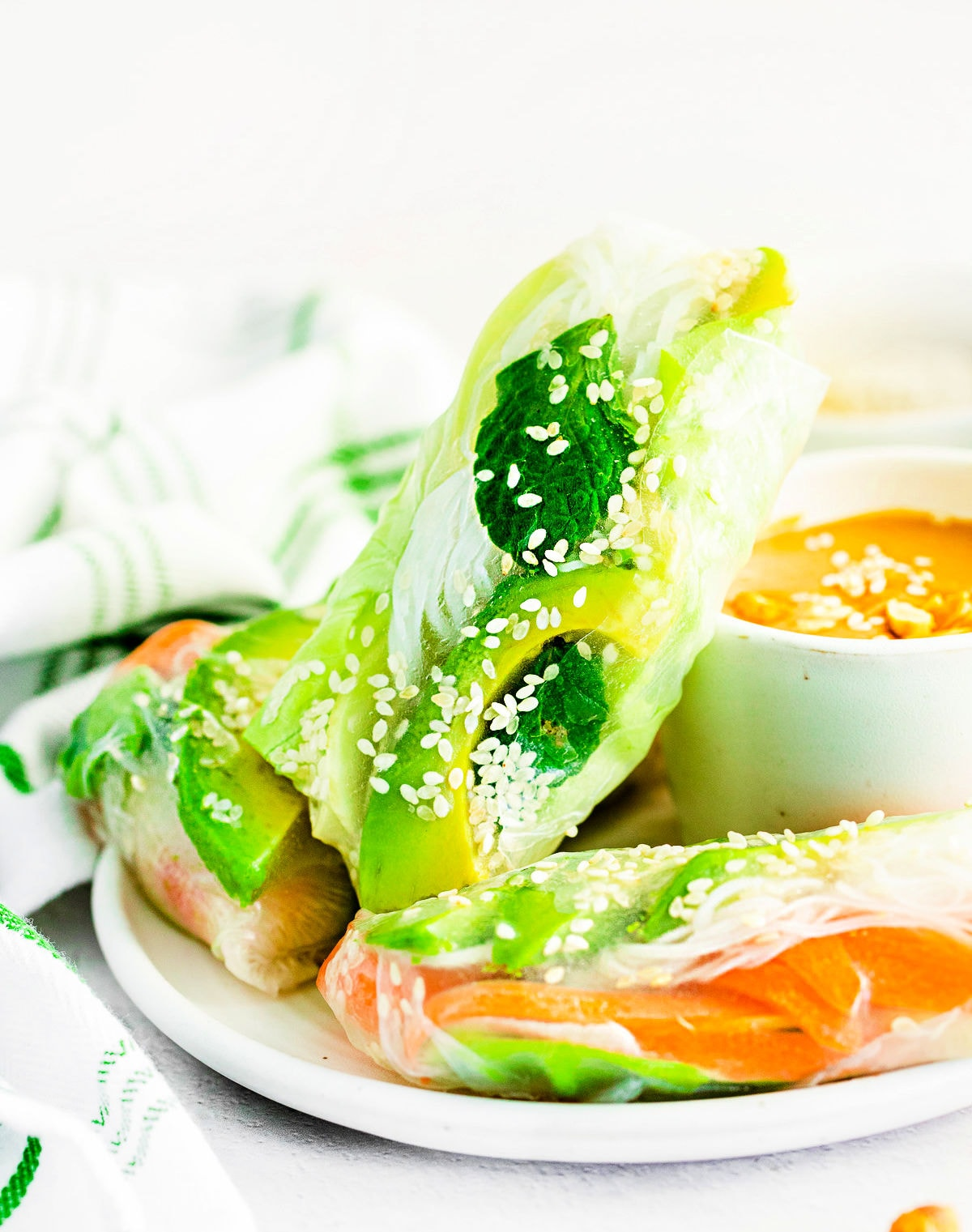 three summer rolls on white plate with peanut dipping sauce.