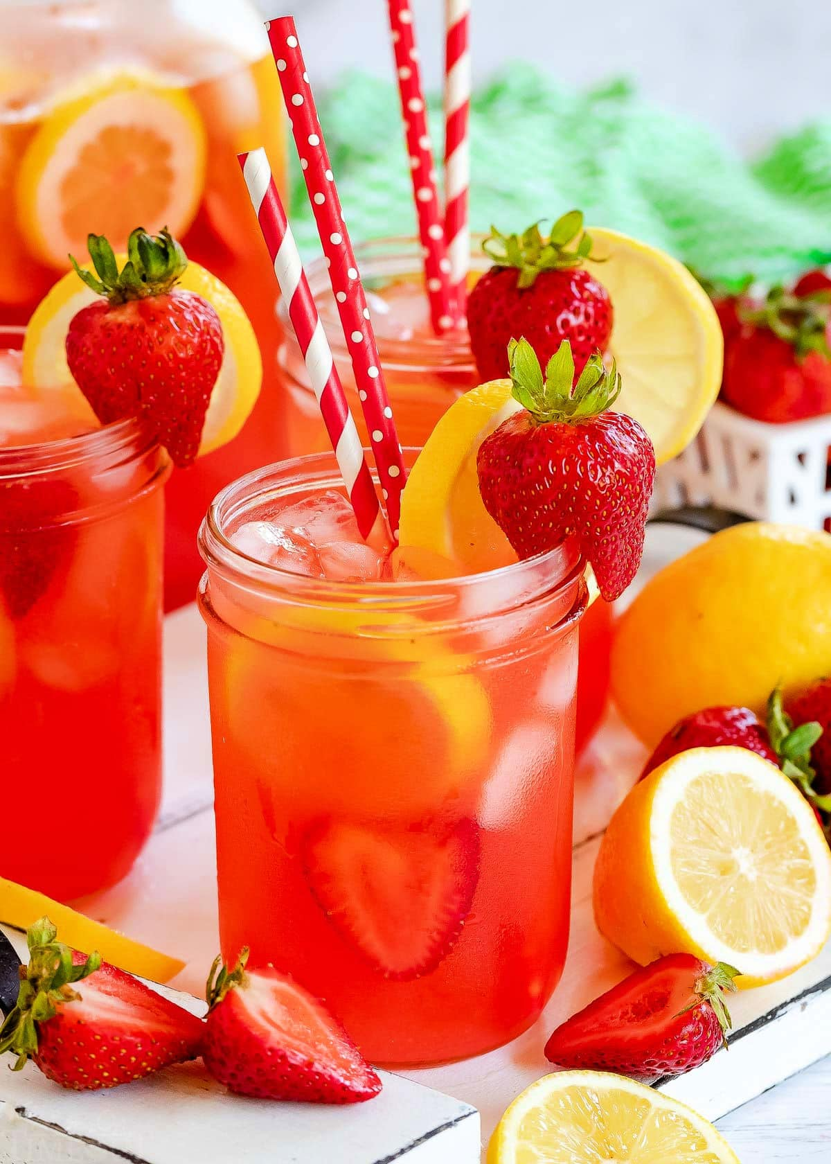 three mason jars filled with strawberry lemonade and topped with lemon slices and fresh strawberries. Red and white paper straws in jars.