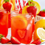 mason jars filled with strawberry lemonade and topped with lemon slices and fresh strawberries. Red and white paper straws in jars.