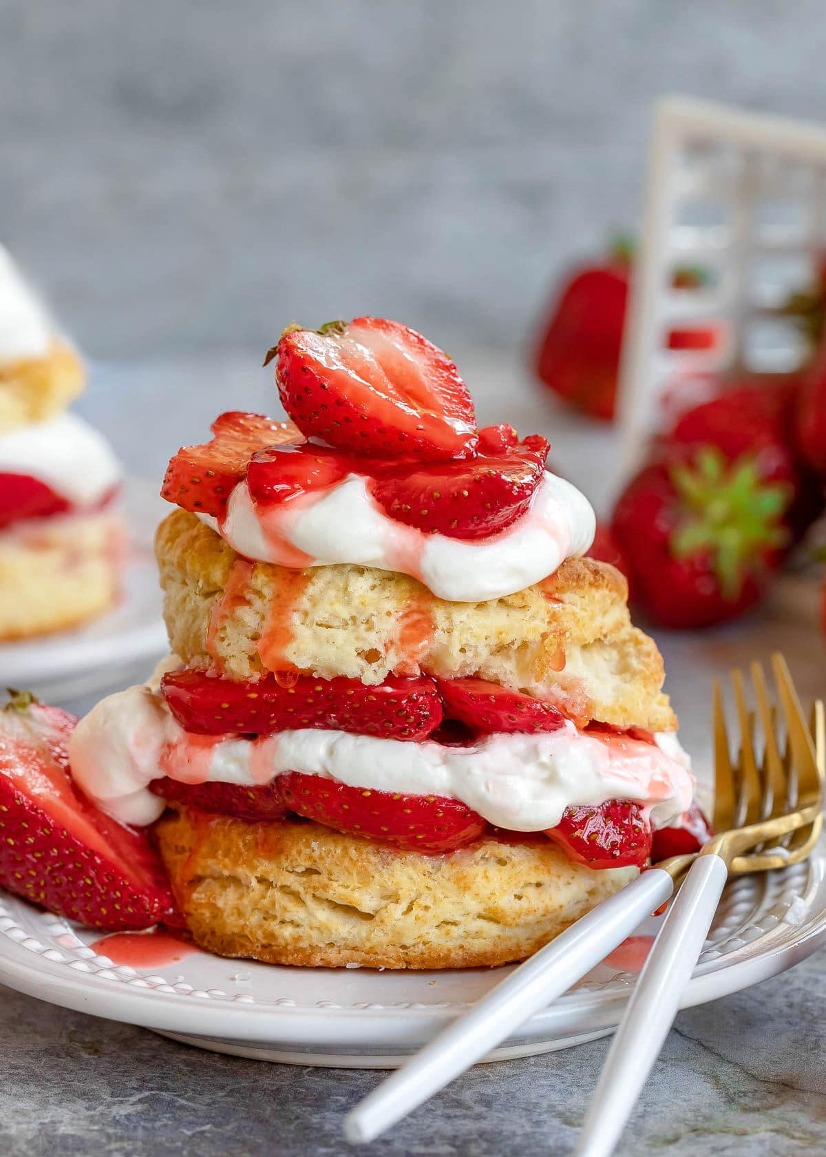 strawberry shortcake made with biscuits and macerated strawberries and fresh whipped cream. Layered on a white plate with two forks sitting on the edge of the plate.