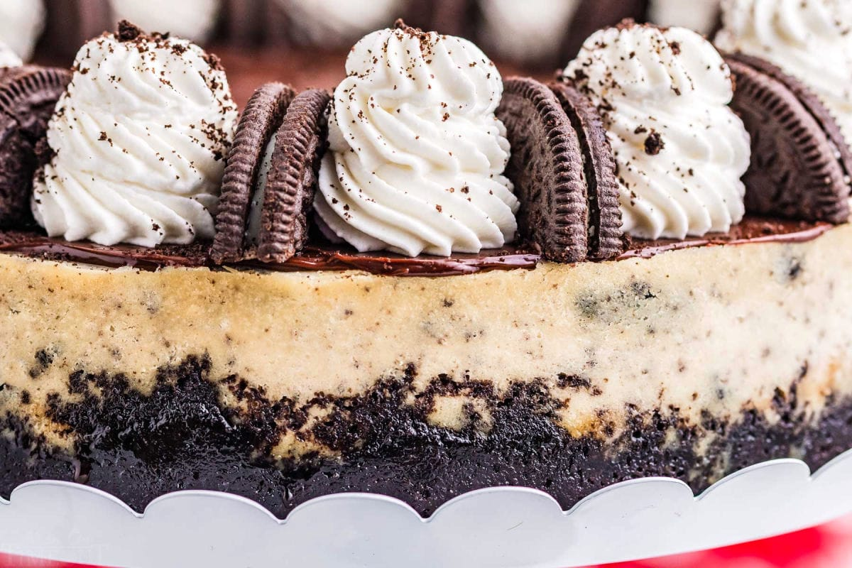 close up look at whipped cream and oreos on top of cheesecake.