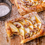 apple tart drizzled with caramel sauce and dusted with powdered sugar on a wood cutting board.