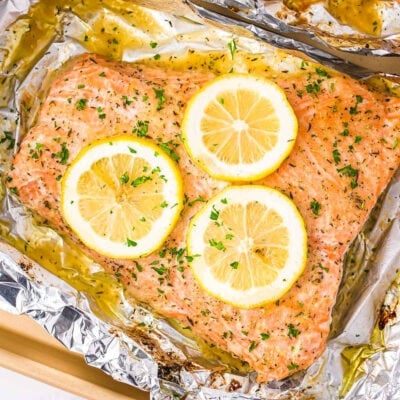 baked salmon in foil topped with lemon slices and fresh parsley.