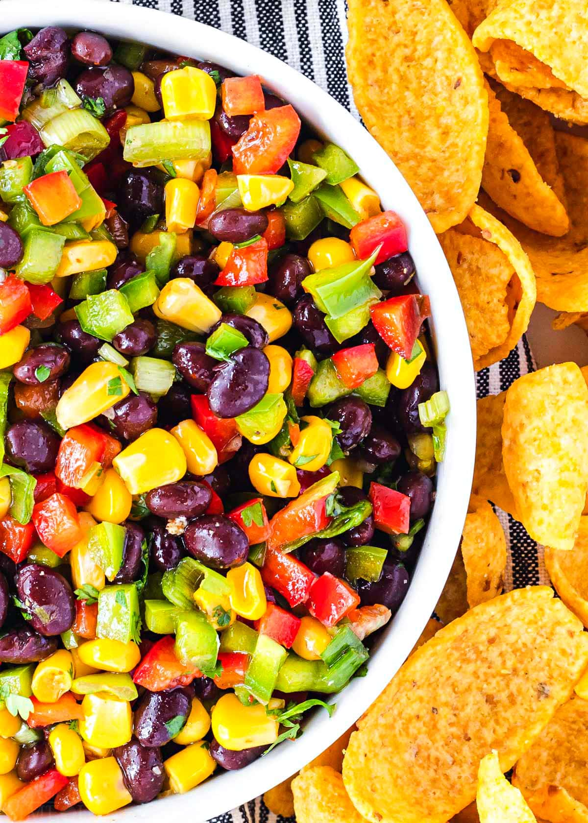 close up look at the vibrant colors of black bean and corn salsa in white bowl with corn chips around the bowl.