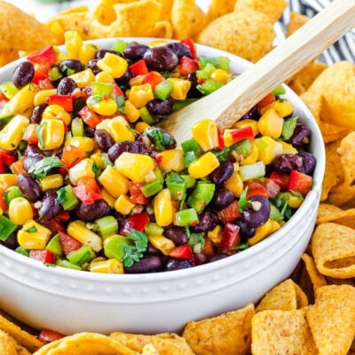 corn salsa with black beans in white bowl and wood spoon inserted. corn chips surrounding the bowl with limes in the background.