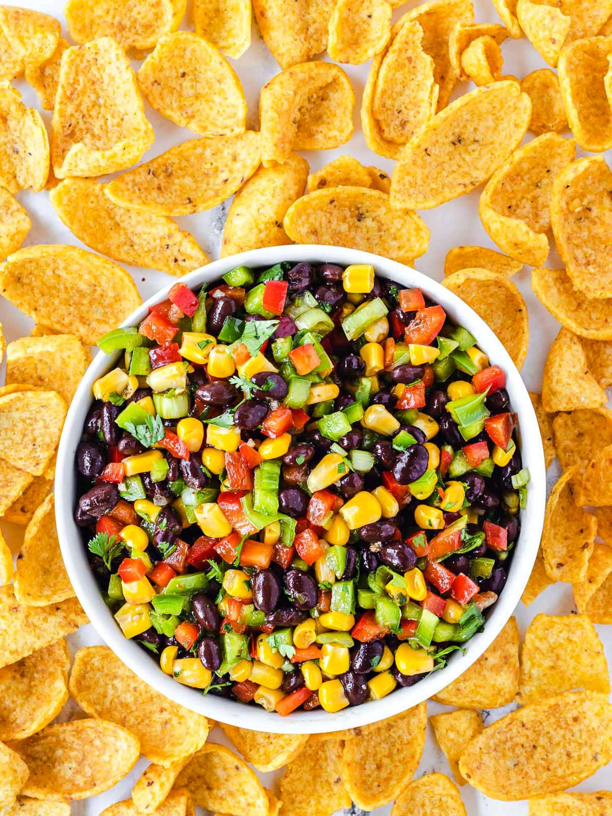 black bean corn salsa in small white serving bowl surround by large corn chips.