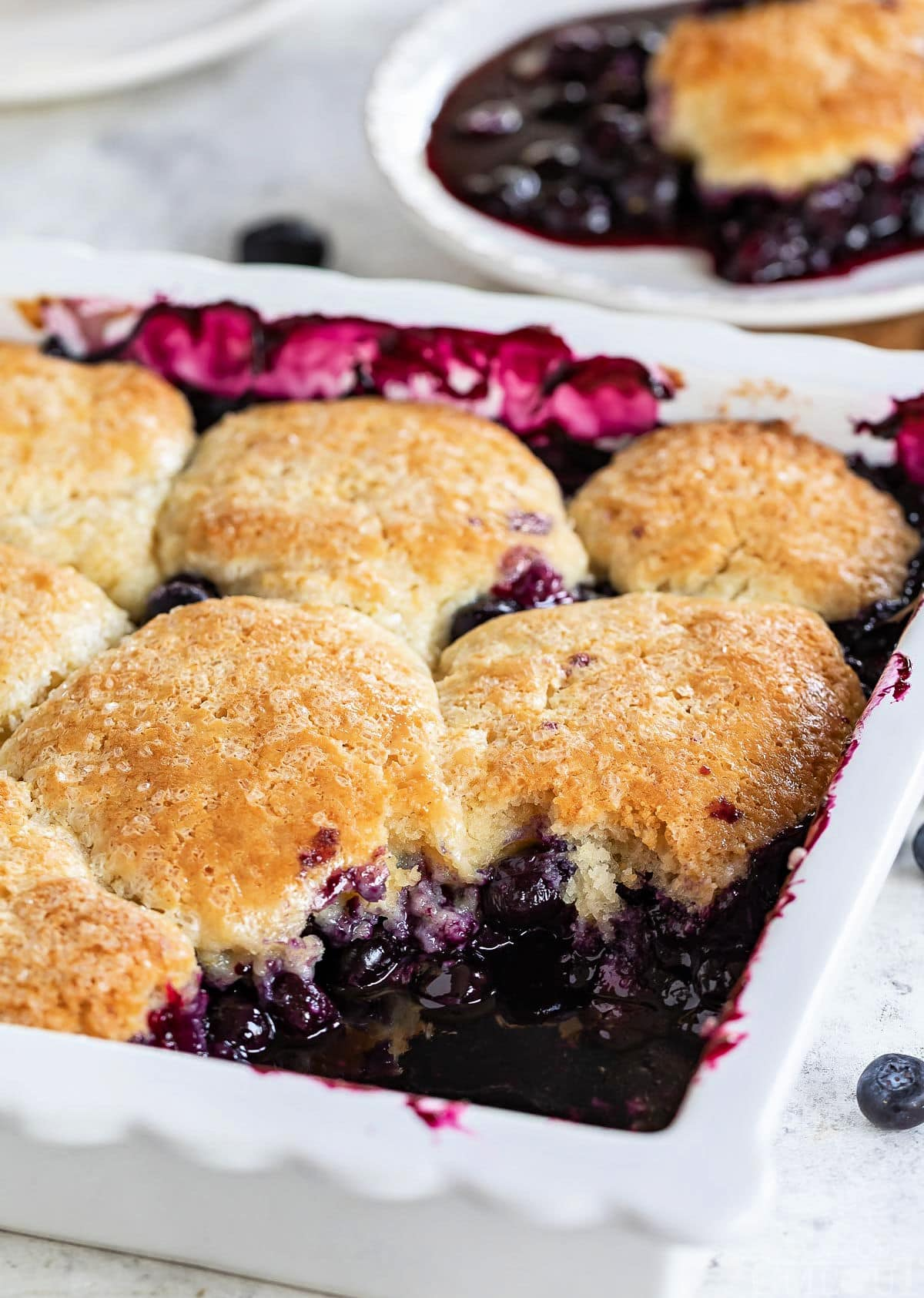 white baking dish with blueberry cobbler and one serving removed and sitting on plate in the background.